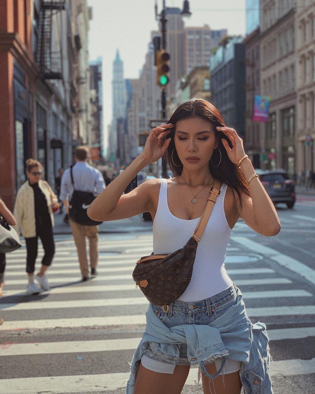 Minh Tú mặc bodysuit màu trắng và quần short jeans