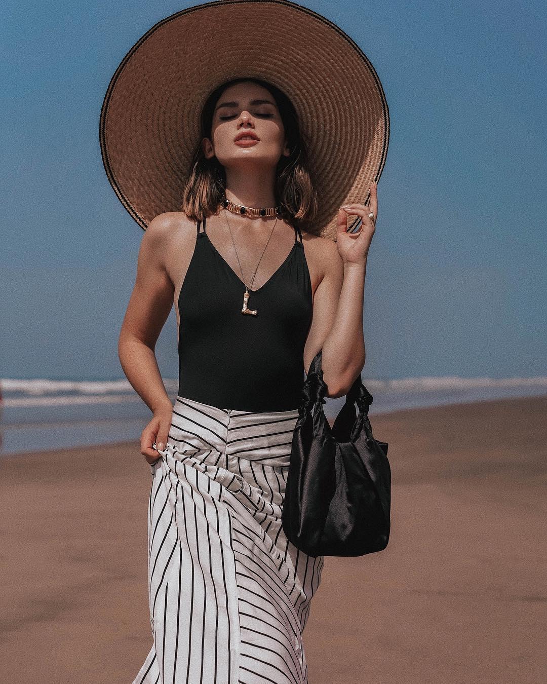 Bodysuit màu đen, chân váy sọc, mũ cói mùa hè