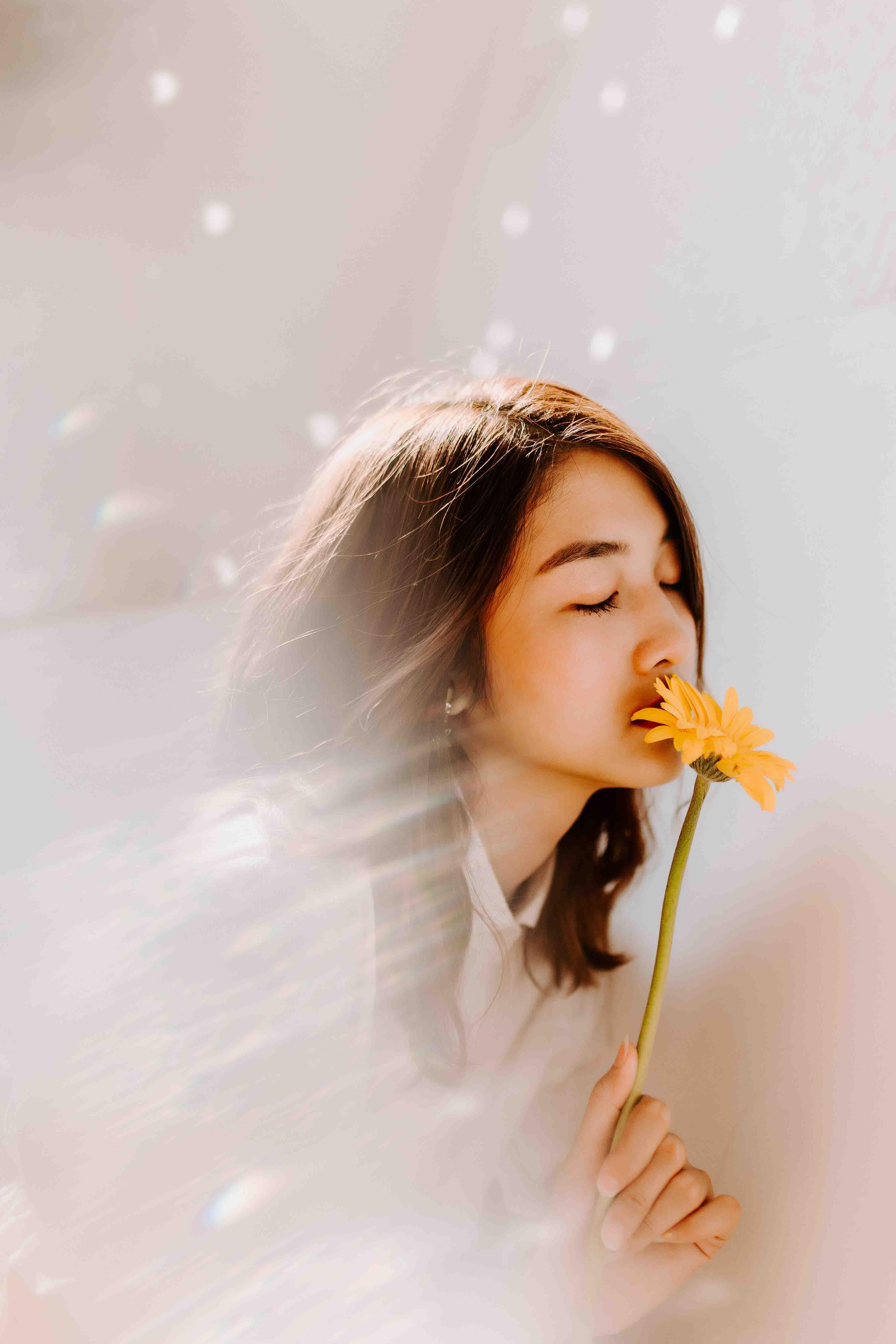 cô gái tổn thương cầm bông hoa màu vàng