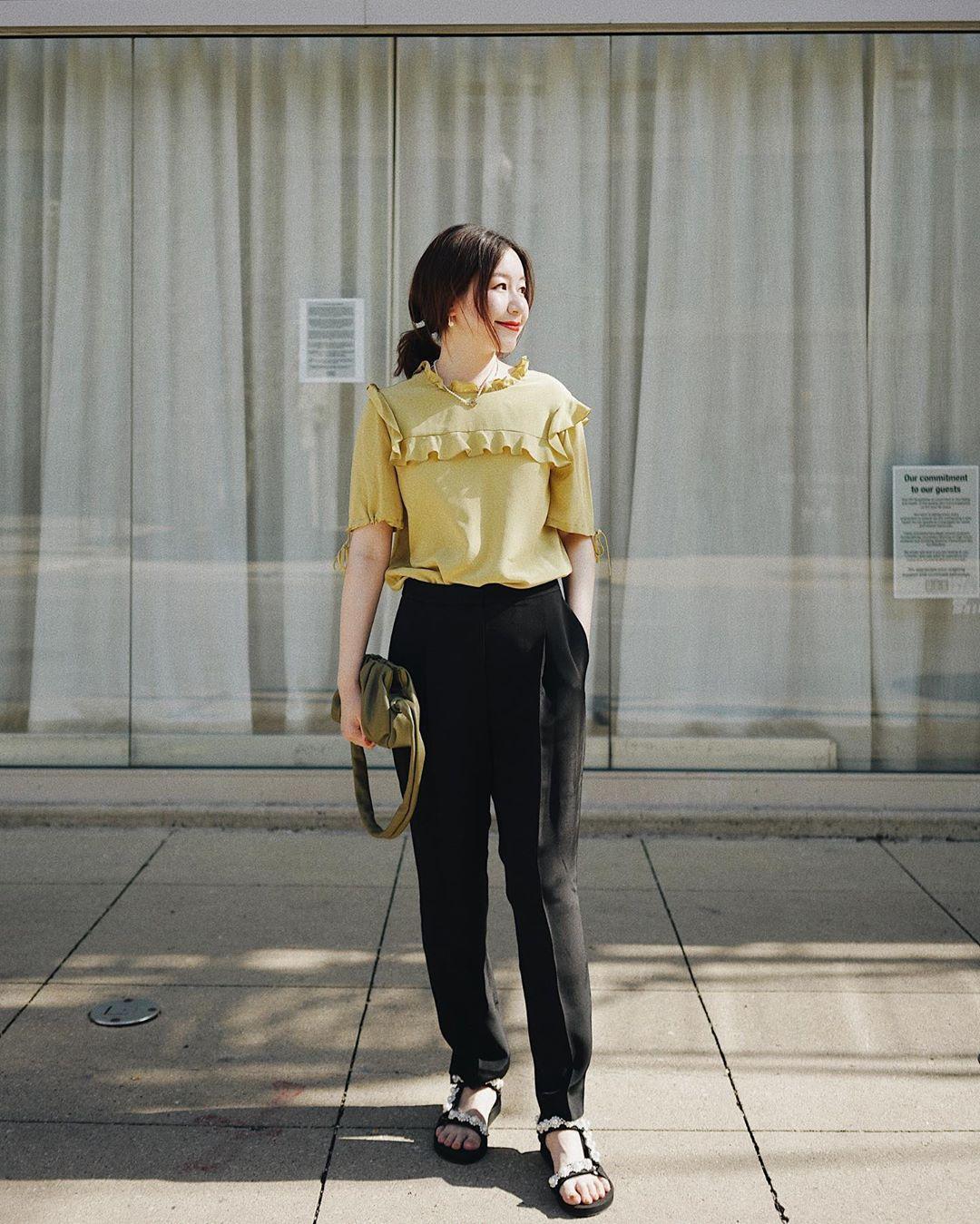 Giày sandals nữ đế thô màu đen phối cùng quần baggy đen và áo vàng