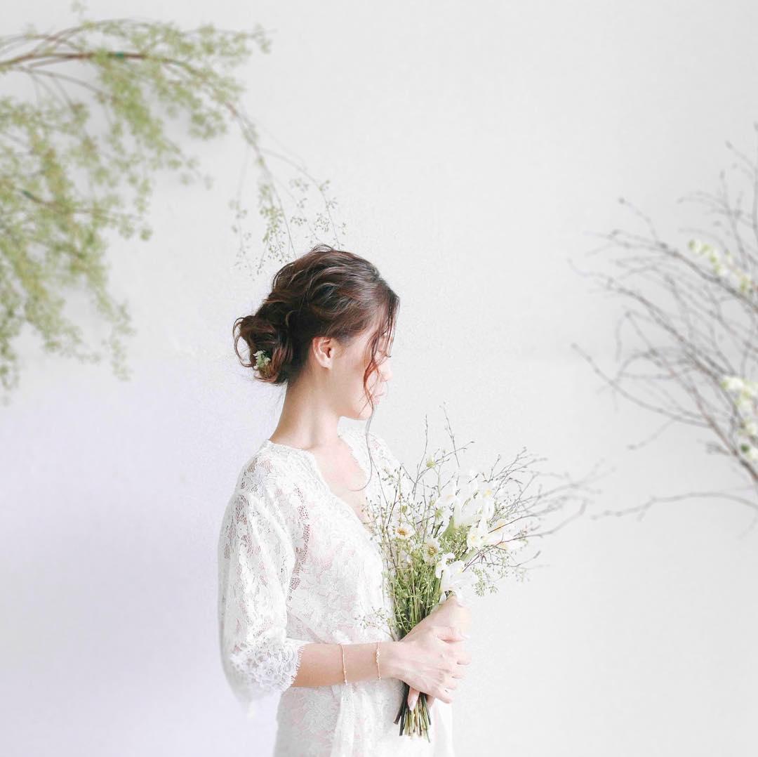 cô dâu mặc váy cưới cầm bó hoa cưới dáng dài làm từ hoa baby breath và cành khô