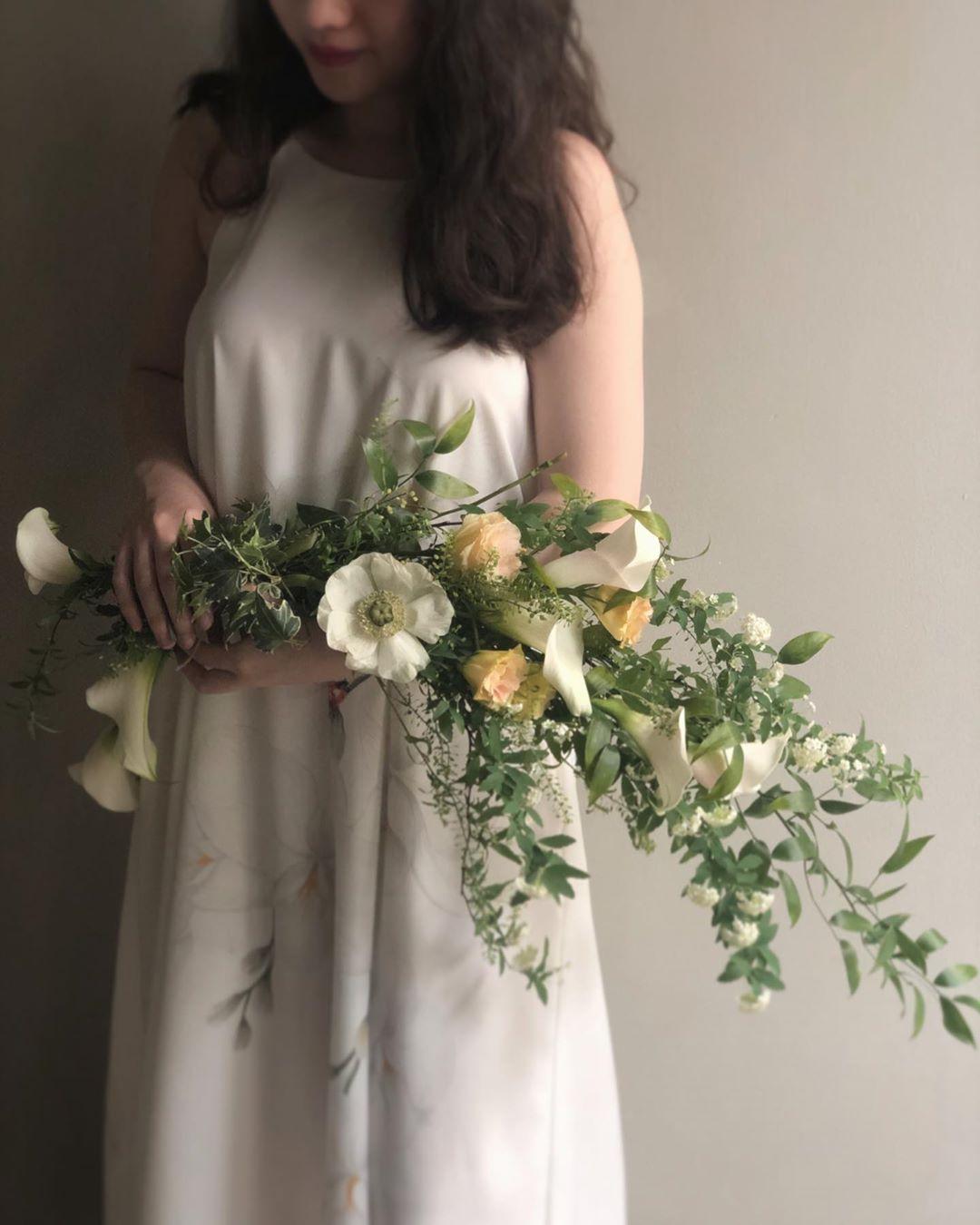 cô gái cầm hoa cưới dáng dài làm từ hoa lily nhỏ và cành lá xanh