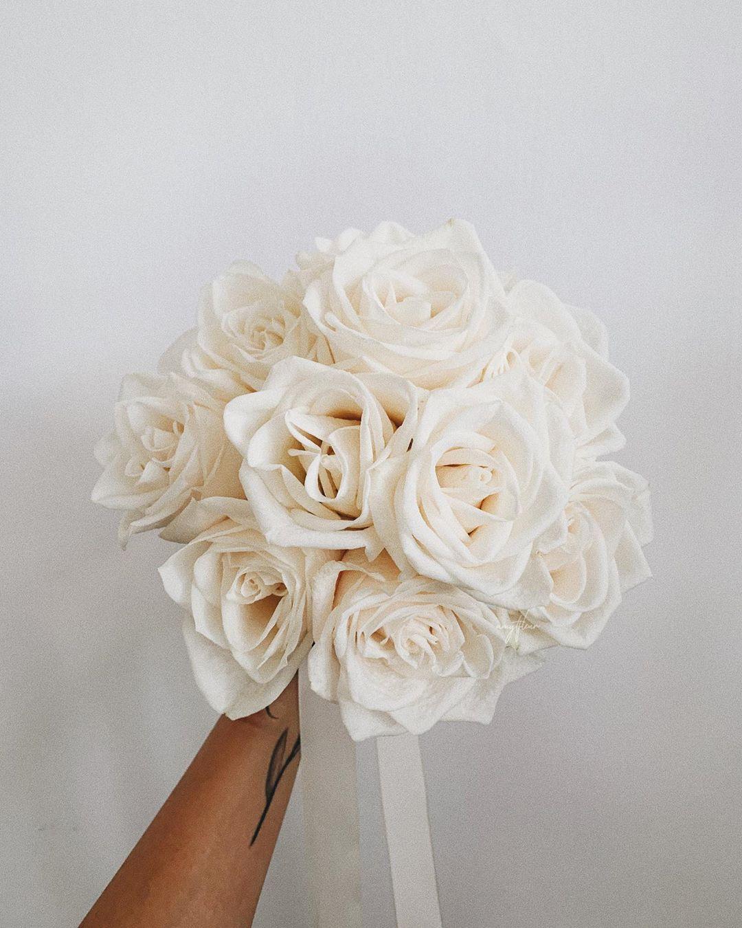 cánh tay cầm bó hoa cưới dáng trong biedermeier làm từ hoa hồng trắng