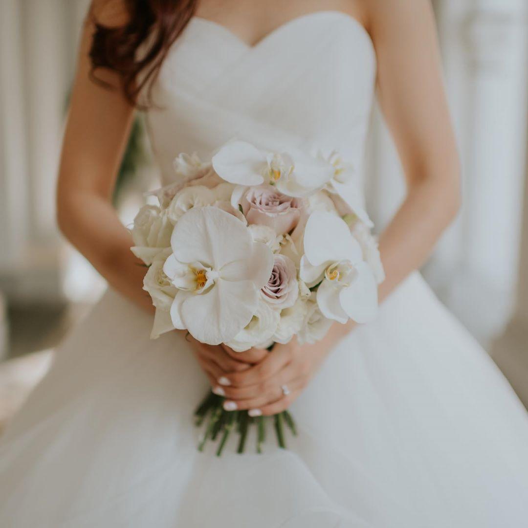 cô dâu cầm hoa cưới posy ngắn làm từ hoa lan trắng