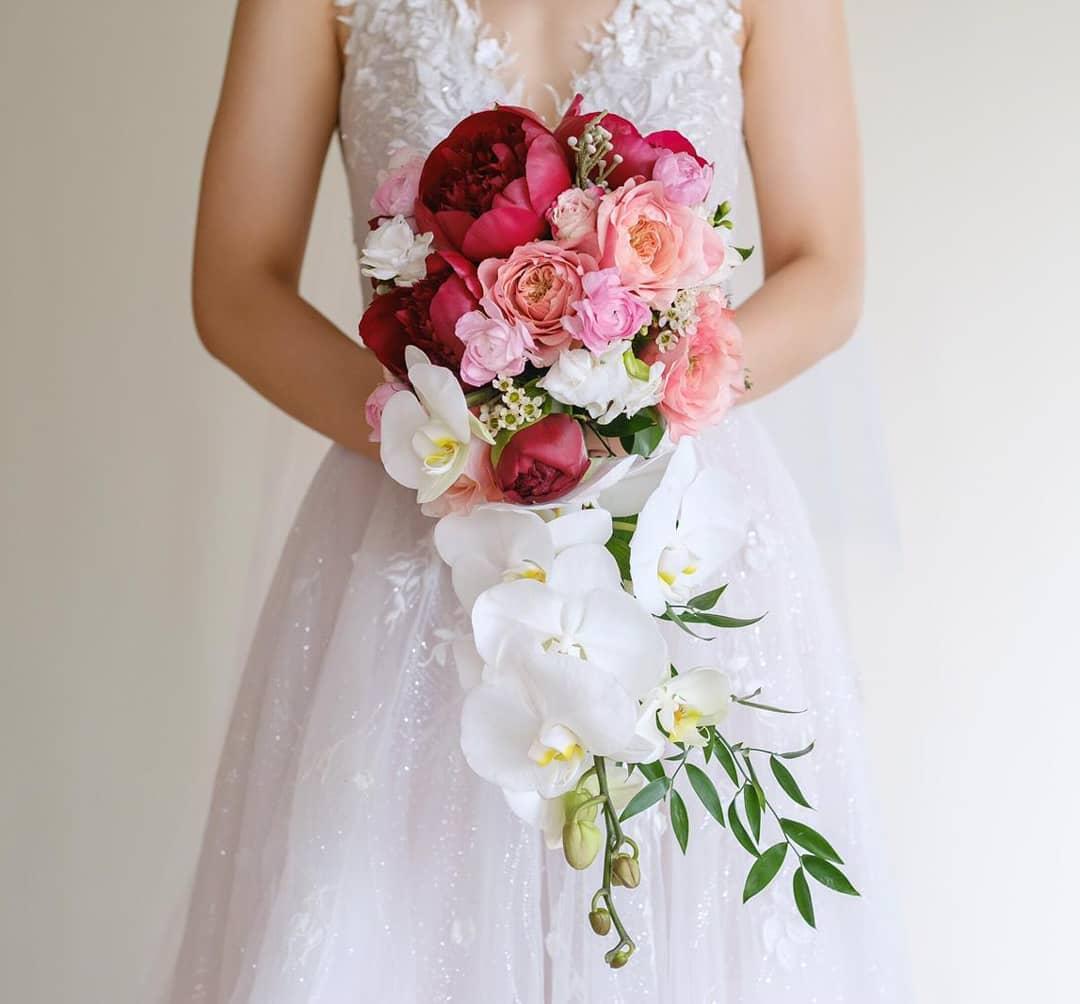cô dâu cầm hoa cưới kiểu thác nước cascade làm từ hoa lan và hoa mẫu đơn đỏ