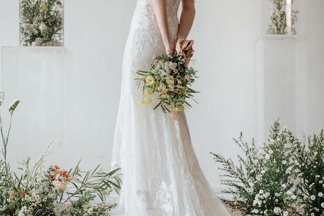 cô dâu cầm hoa cưới theo kiểu tự nhiên sau lưng