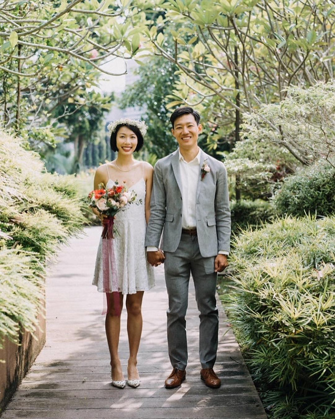 cô dâu mặc đầm cưới ngắn cầm bó hoa cưới kiểu tự nhiên nắm tay chú rể