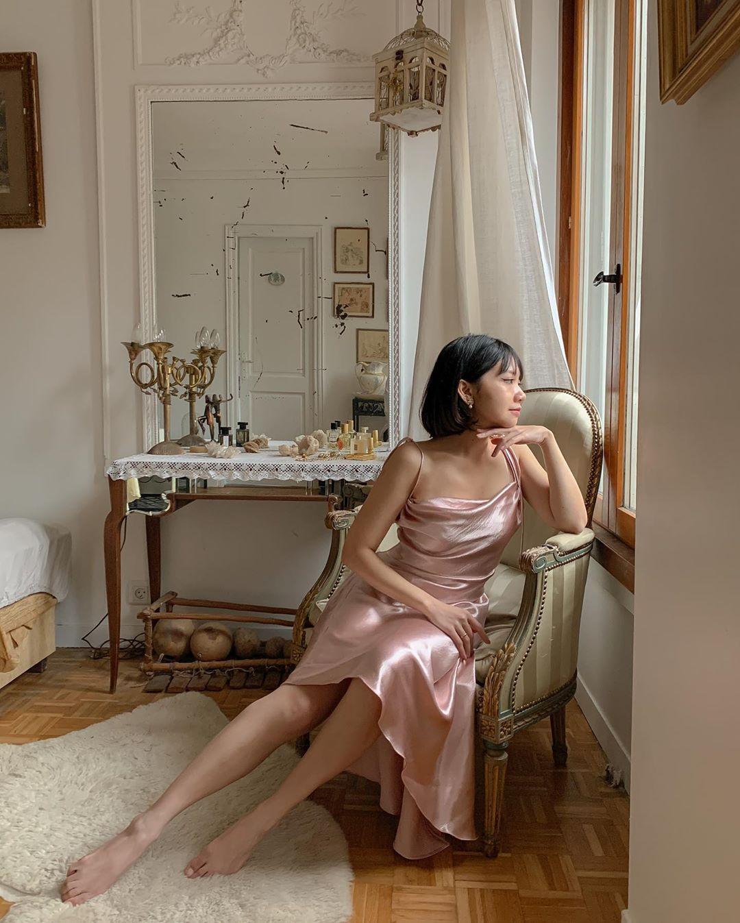 hegia mặc đầm slip dress lụa bóng màu hồng thạch anh ngồi trên ghế sofa