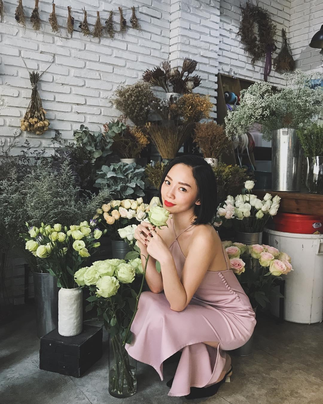 tóc tiên mặc đầm slip dress lụa cổ yếm màu hồng thạch anh rose quartz trong tiệm hoa
