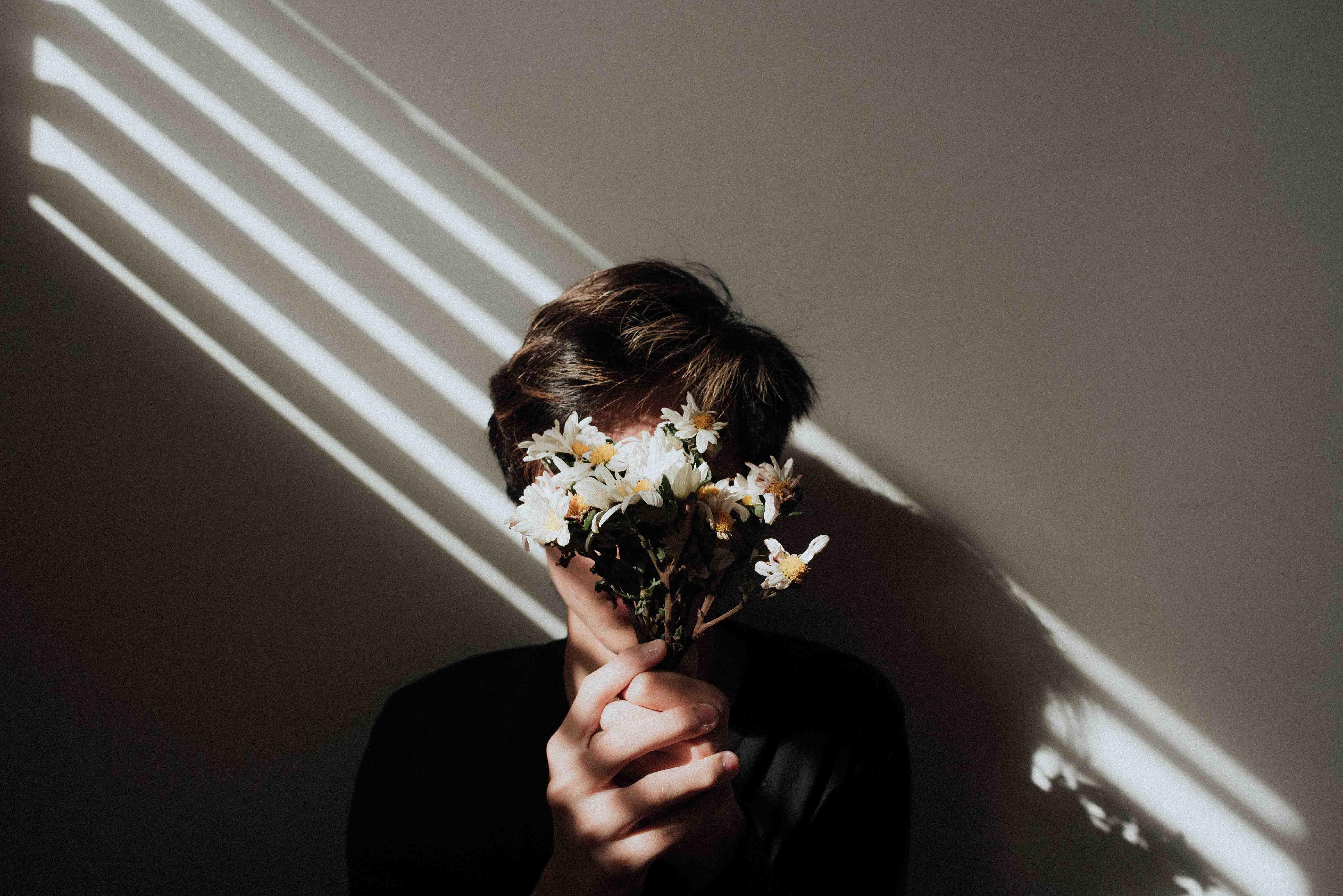 cô gái cầm bó hoa che mặt vì cảm xúc