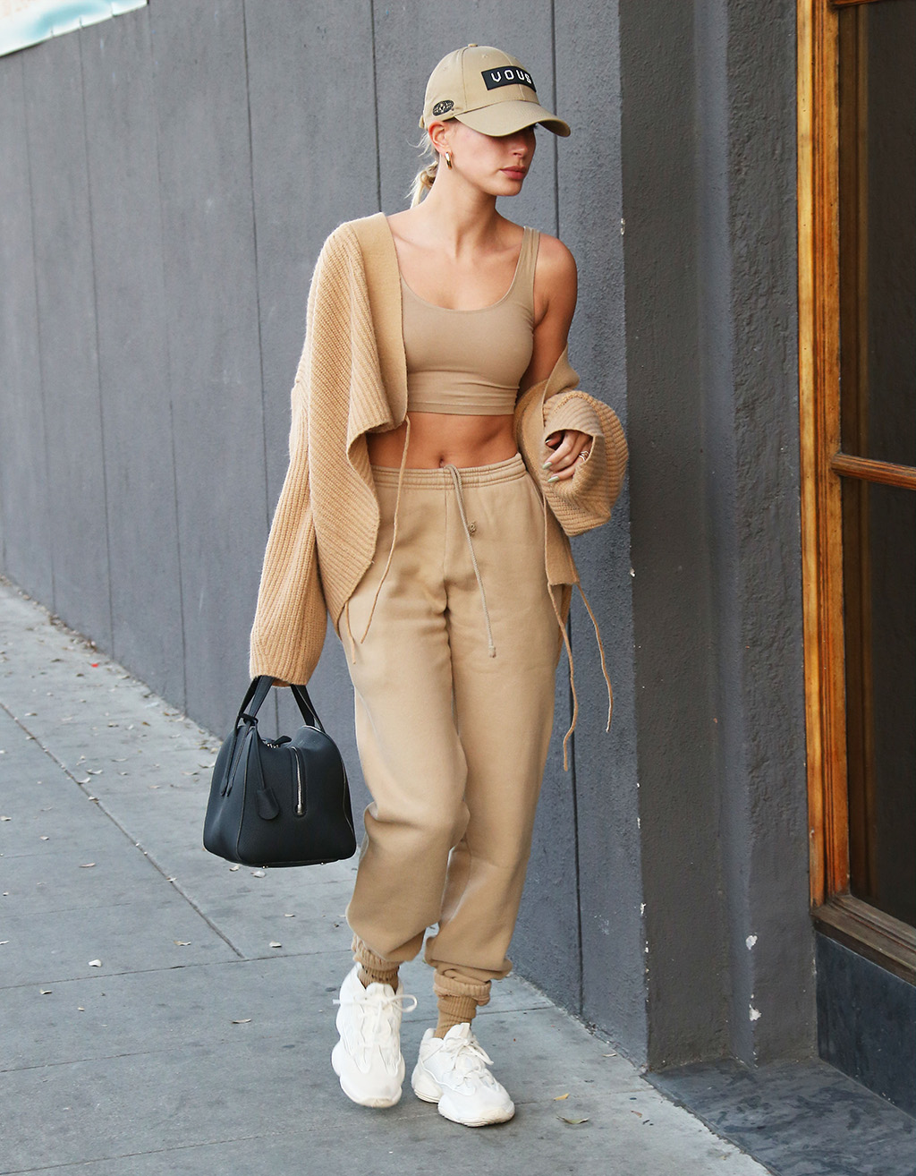 Hailey Bieber mặc quần jogger và bra thể thao màu be