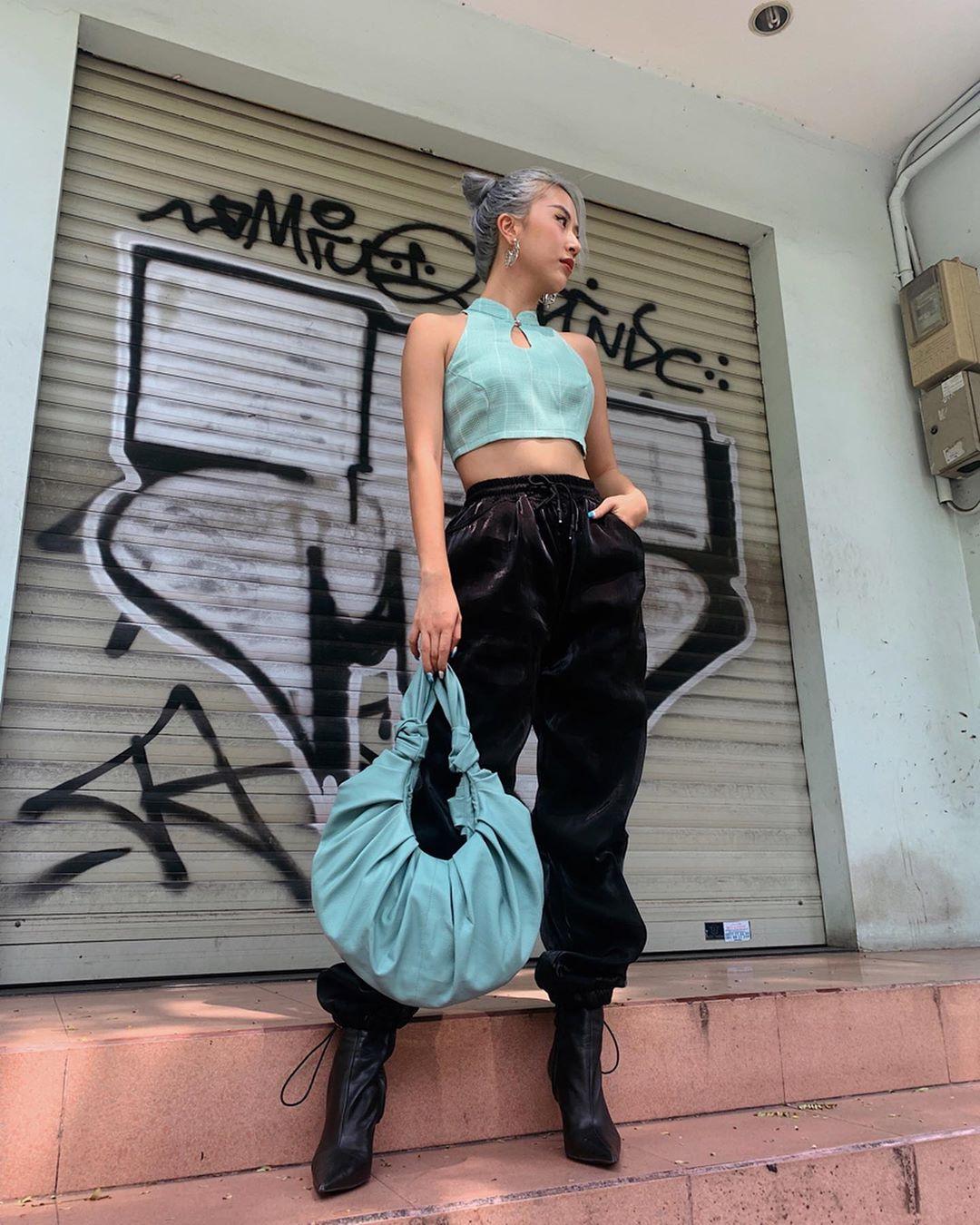Quỳnh Anh Shyn mặc croptop cổ yếm màu xanh và quần jogger đen