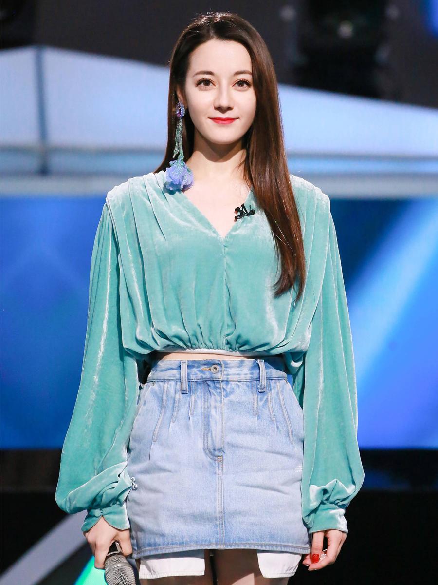 Địch Lệ Nhiệt Ba mặc áo xanh, chân váy jean, đeo hoa tay dáng dài hình hoa