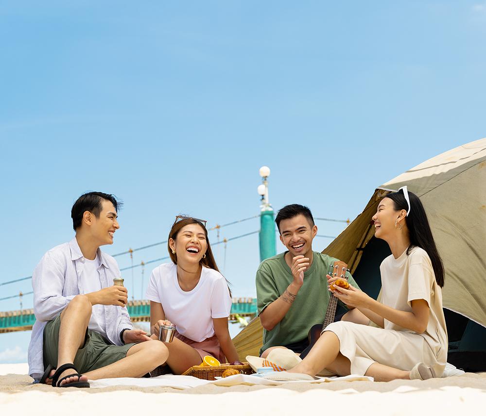 bốn người bạn đi picnic bên bãi biển mùa hè