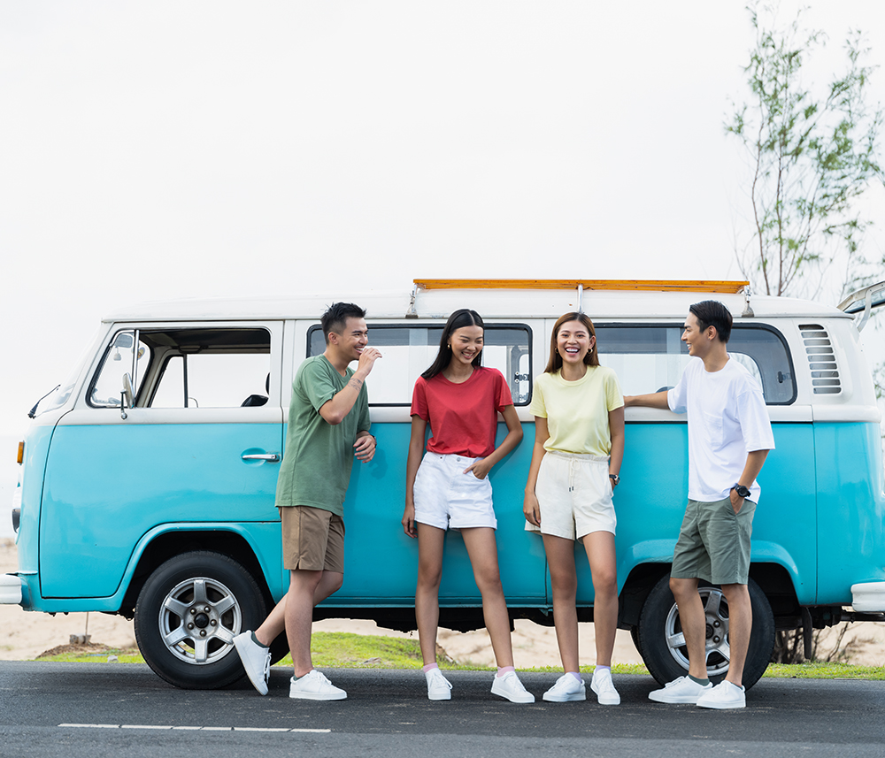 bốn người bạn vui vười bên cạnh xe van du lịch mùa hè
