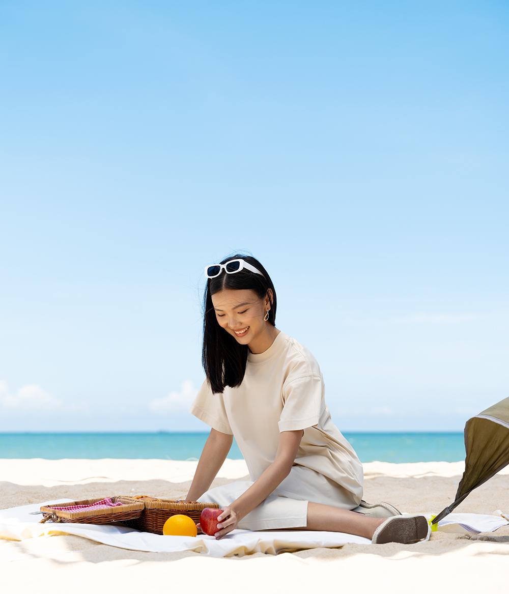 cô gái mặc đầm suôn dài màu be ngồi trên bãi biển mùa hè