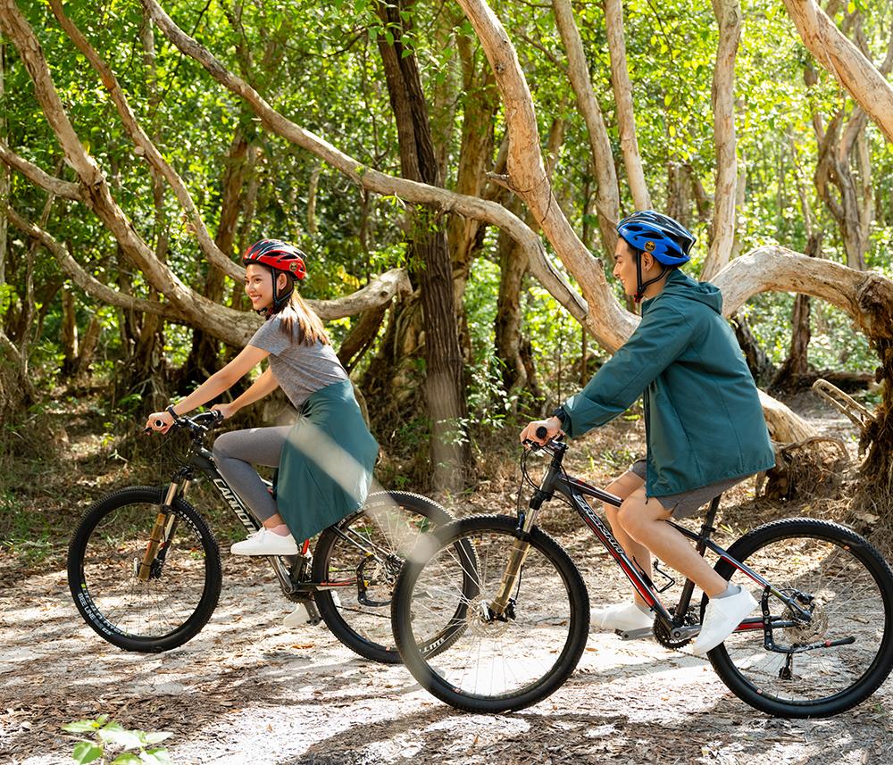 hai người mặc áo thun quần thể thao đạp xe khám phá rừng mùa hè