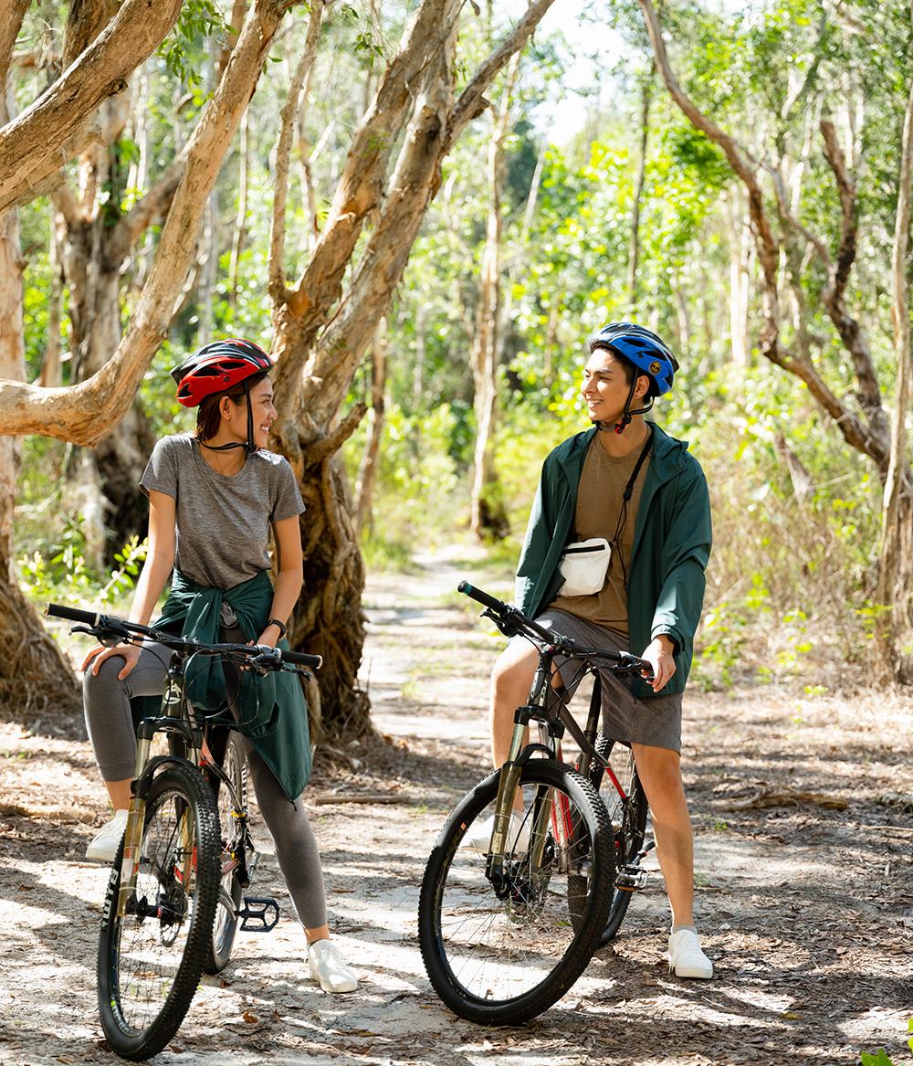 hai người mặc đồ thể thao đạp xe thảm hiểm khu rừng mùa hè