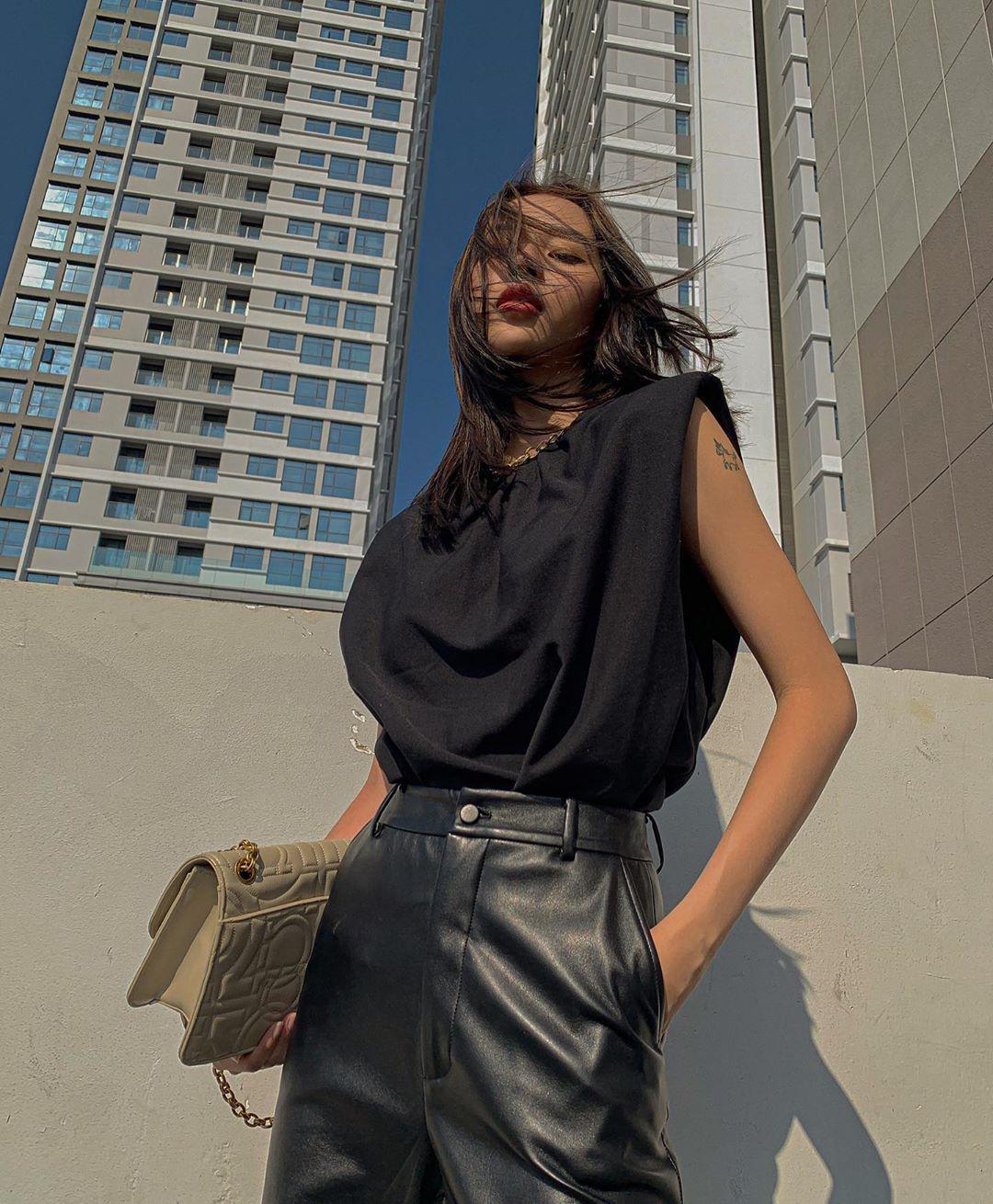 Phí Phương Anh diện áo thun độn vai màu đen và quần da