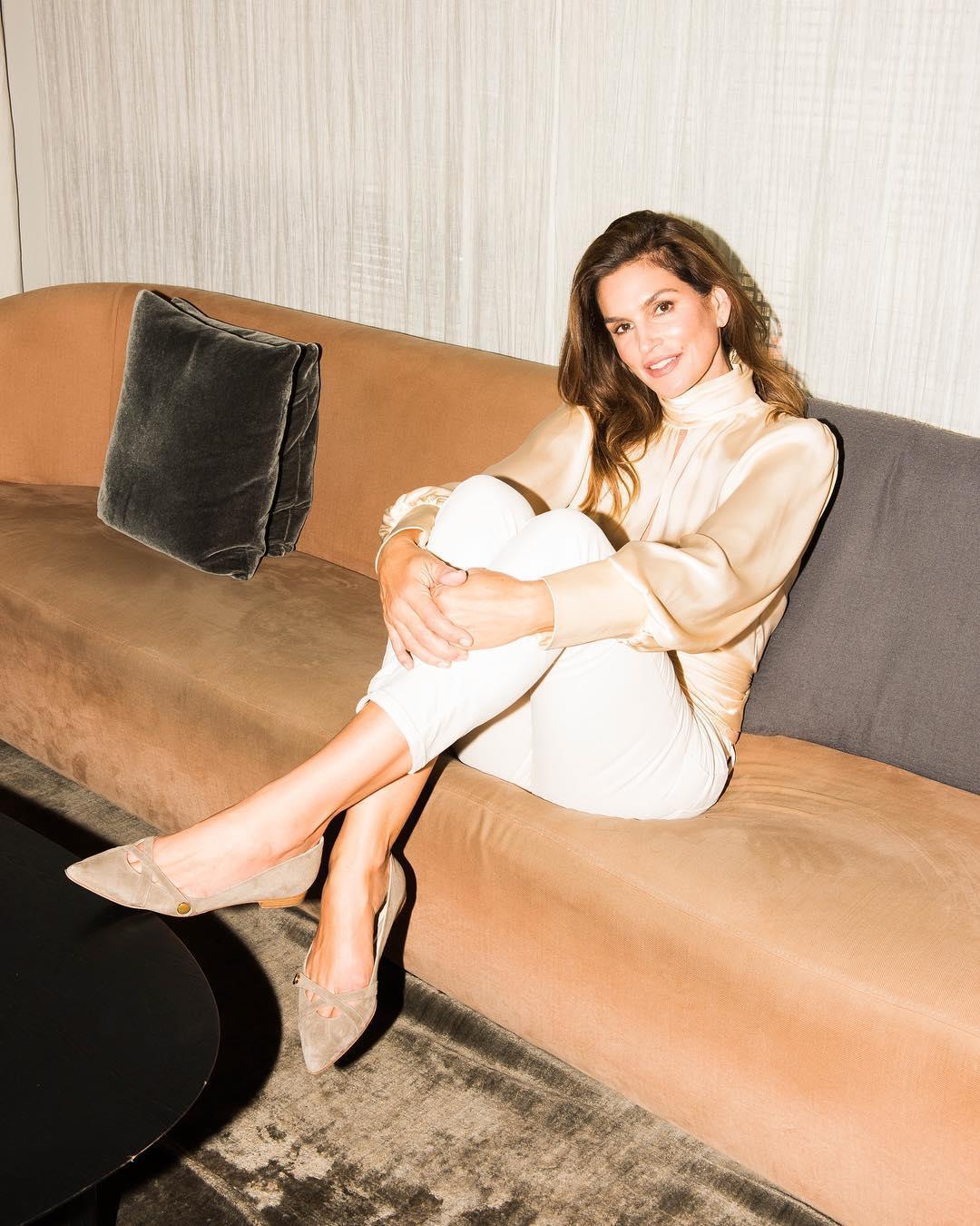 những câu nói hay của cindy crawford mặc áo satin mang giày mũi nhọn ngồi trên ghế sofa