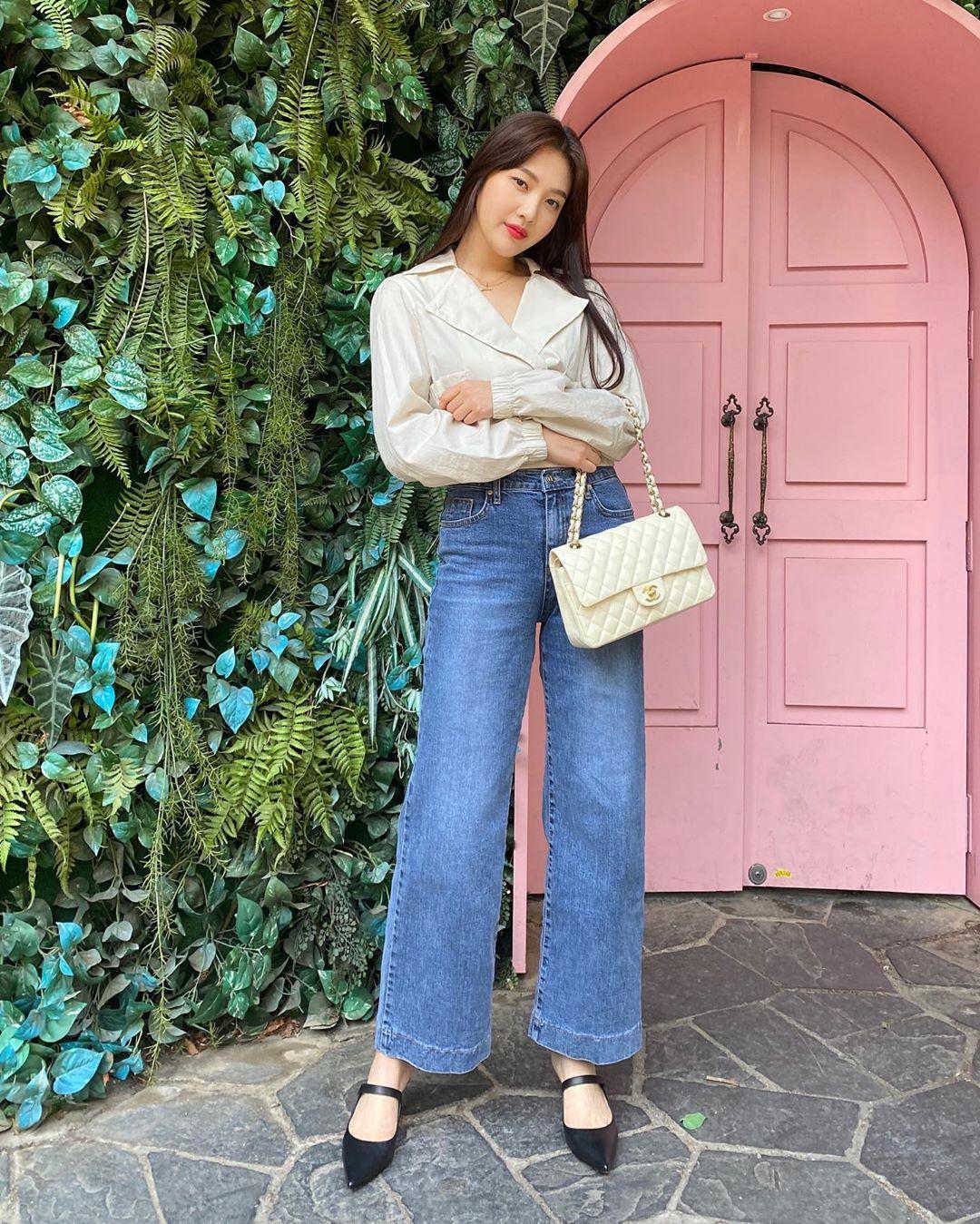 Joy mặc sơ mi trắng, quần jeans ống rộng, đeo túi Chanel