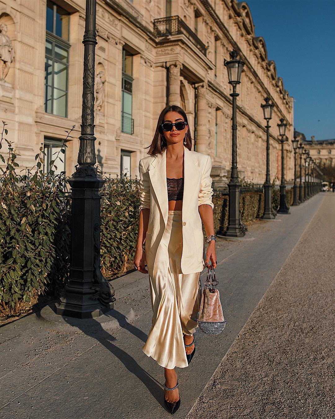 camila coelho mặc chân váy vải lụa áo bralette và áo blazer trắng