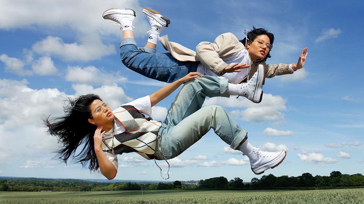 hai cô gái mang giày converse run star hike nhảy trên đồng cỏ