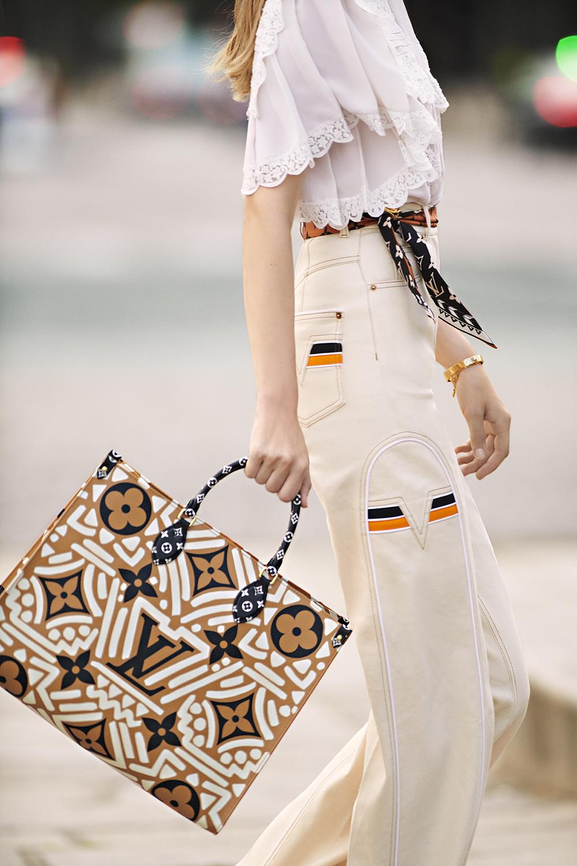 cô gái mang túi tote louis vuitton onthego họa tiết lv crafty màu kem caramel