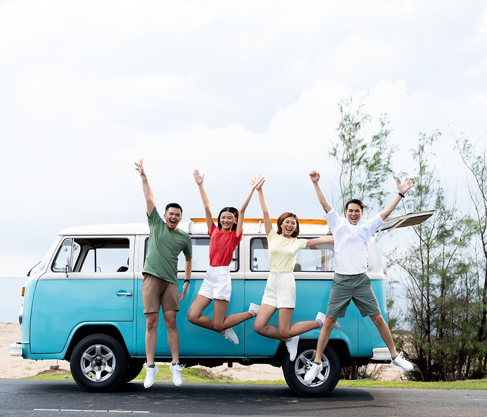 4 người bạn mặc đồ uniqlo nhảy bên xe van du lịch