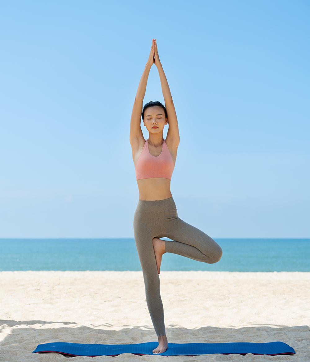 cô gái mặc trang phục uniqlo đang tập yoga bên bãi biển