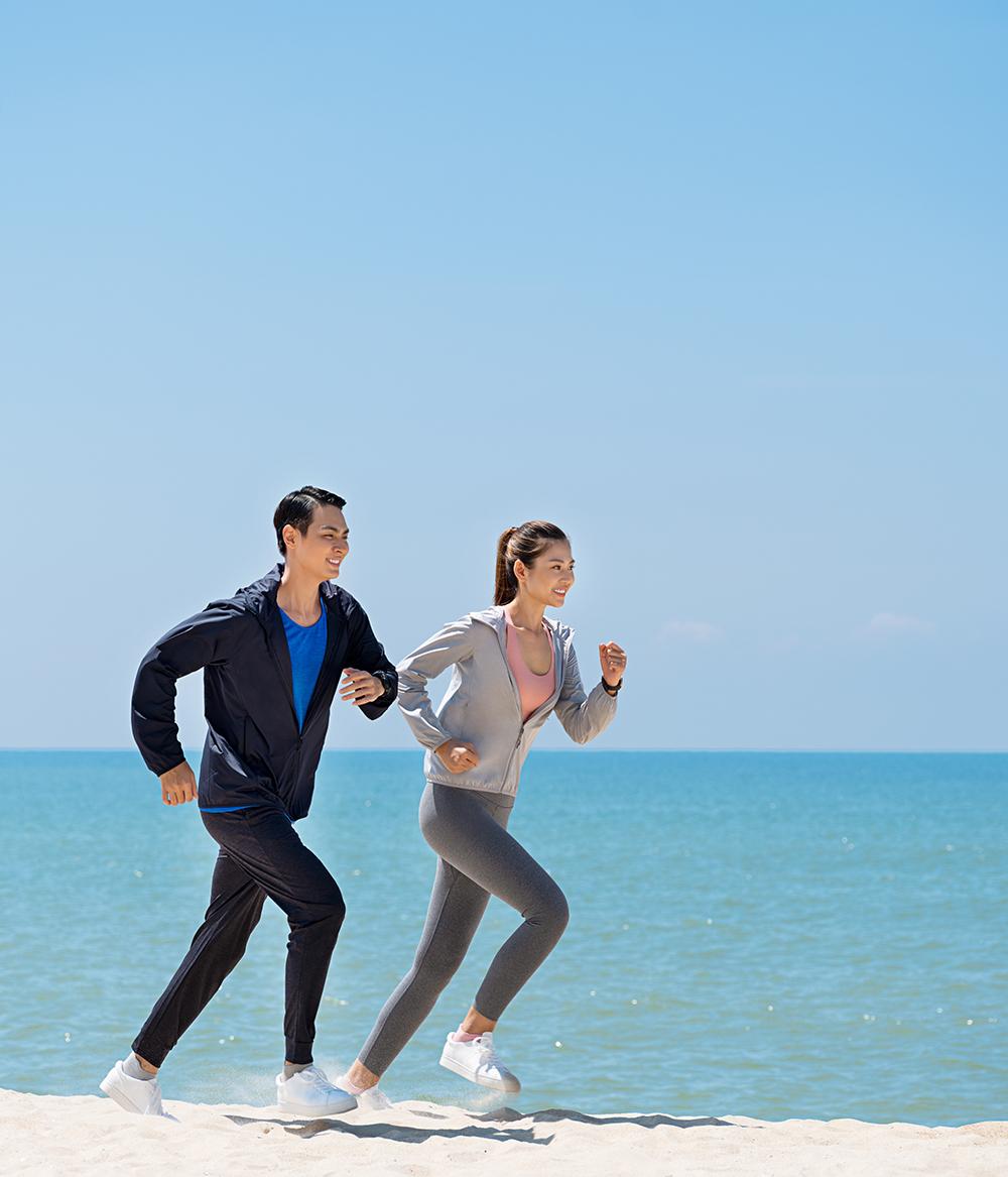hai người mẫu mặc áo khoác uniqlo đang chạy bộ bên bờ biển