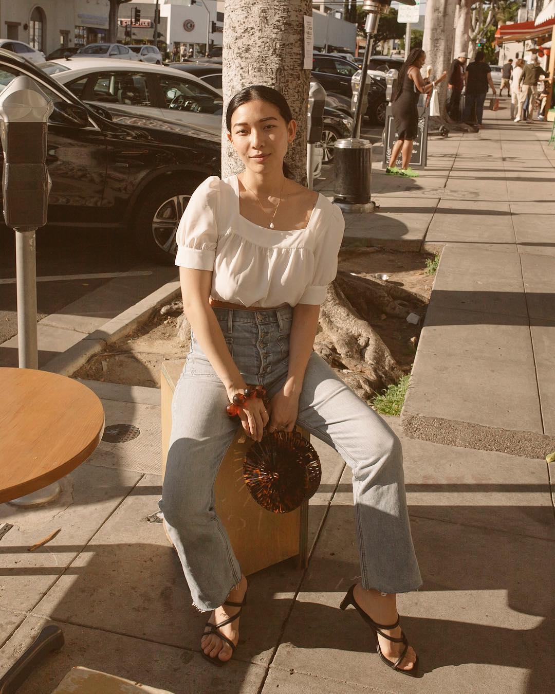 cô gái mặc áo nữ cổ vuông tay phồng màu trắng và quần jeans