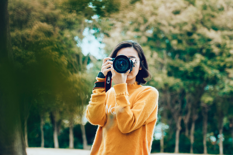 nhãn thông cô gái cầm máy ảnh