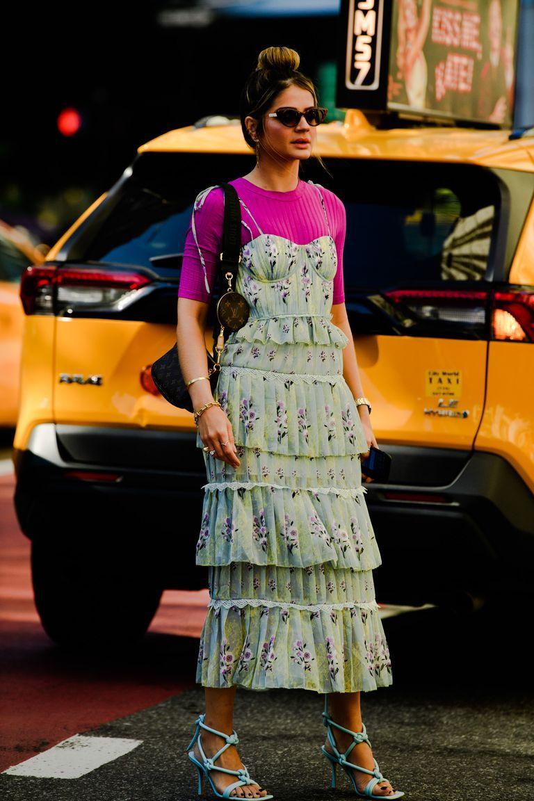 Cô gái mặc váy xòe hai dây in hoa và áo thun tím