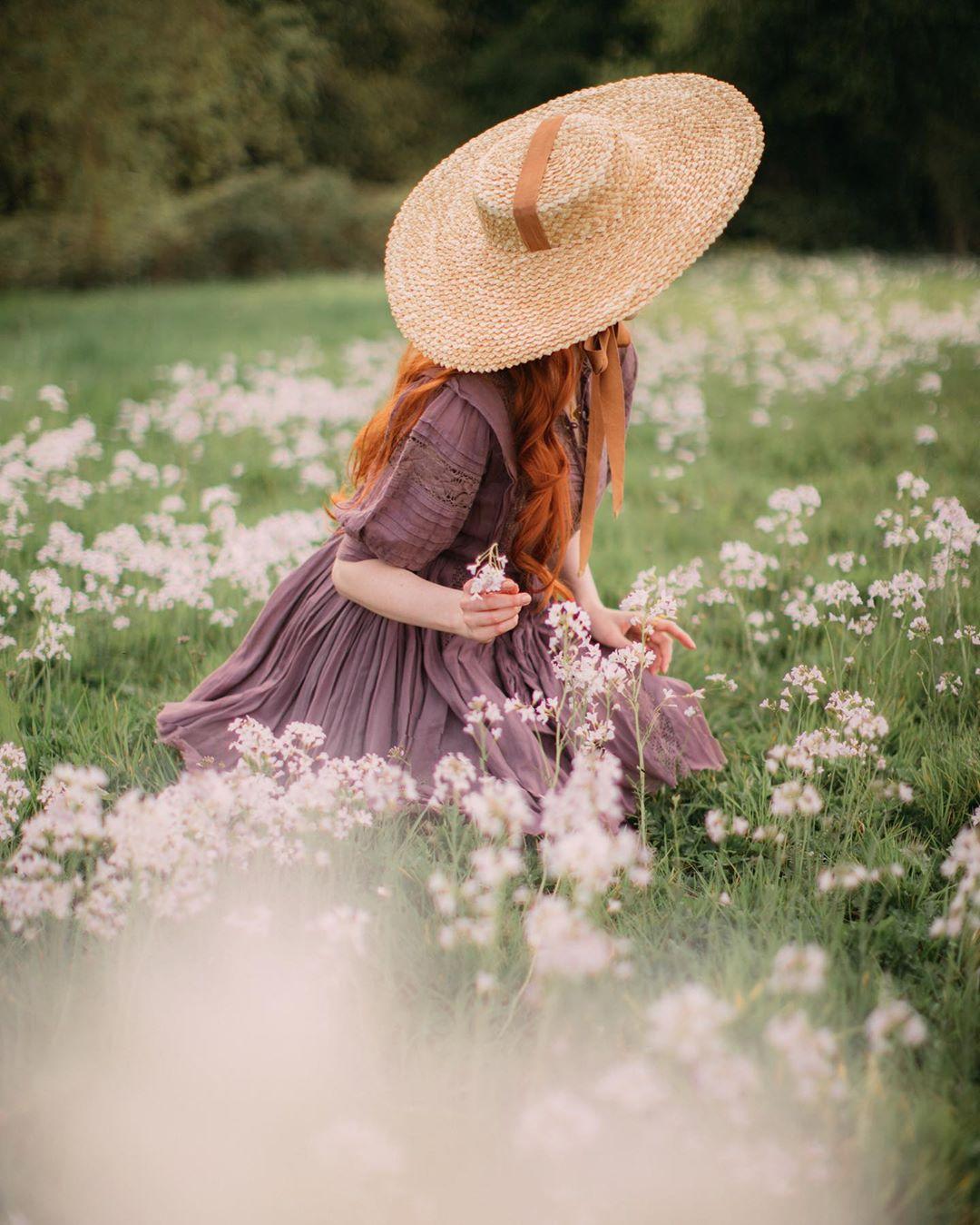 Cô gái mặc váy tím, đội mũ cói rộng vành phong cách thời trang Cottagecore