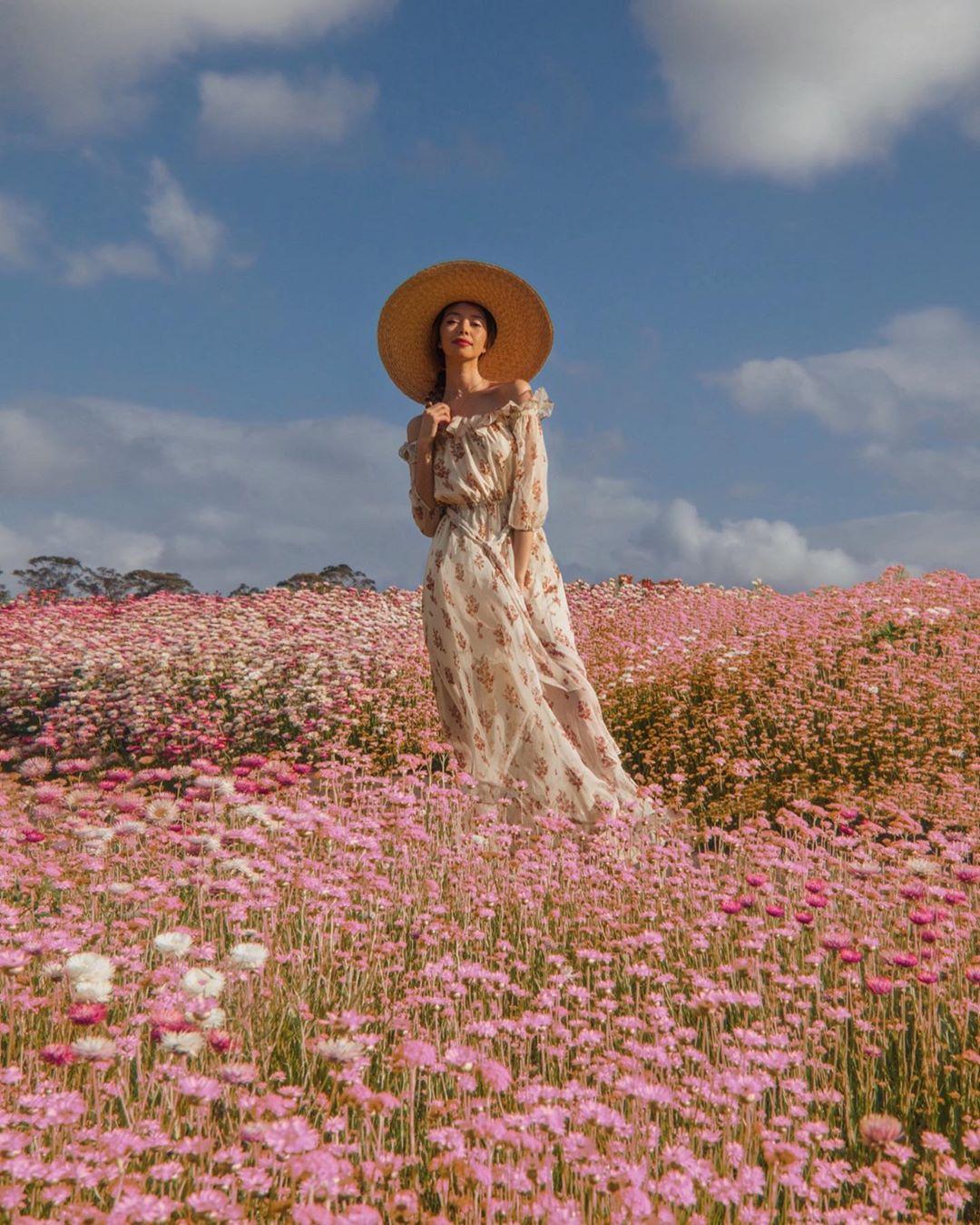 Cô gái mặc váy voan hoa phong cách thời trang Cottagecore trễ vai, đội mũ rộng vành trên cánh đồng hoa
