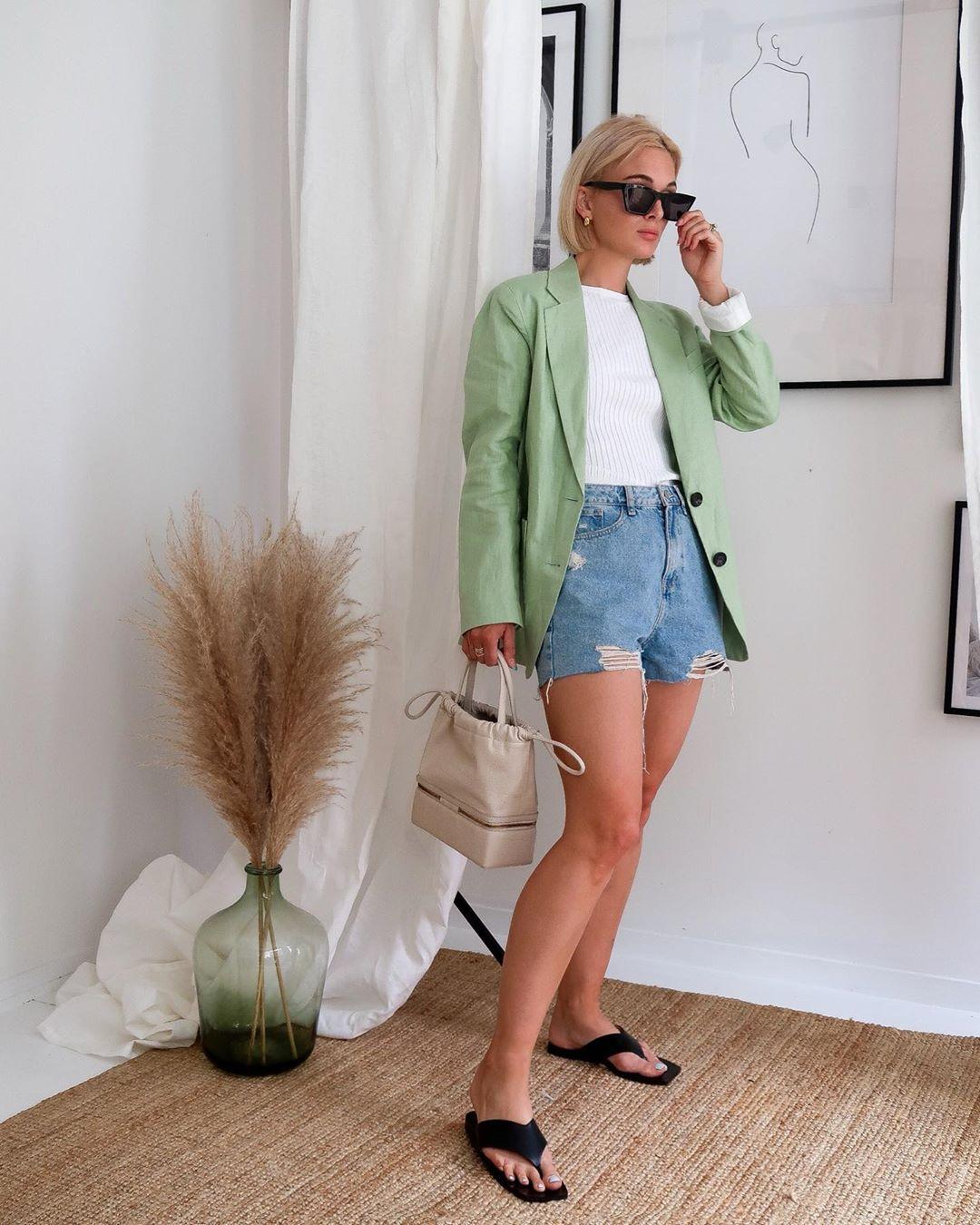 Cô gái mặc short jeans, blazer xanh lá, mang dép nữ xỏ ngón màu đen