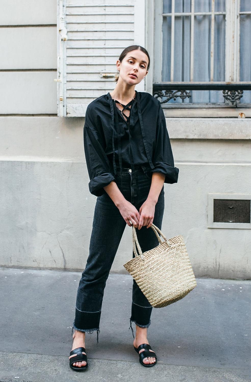 Cô gái mặc áo đen, quần đen, mang dép nữ quai ngang