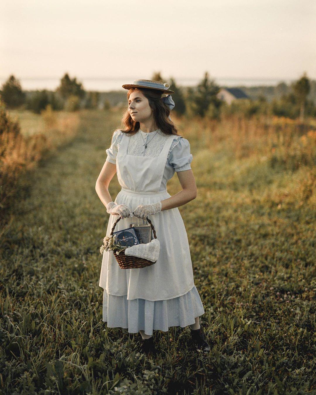 cô gái với phong cách thời trang cottagecore đầm xanh tạp dề trắng giữa thảo nguyên