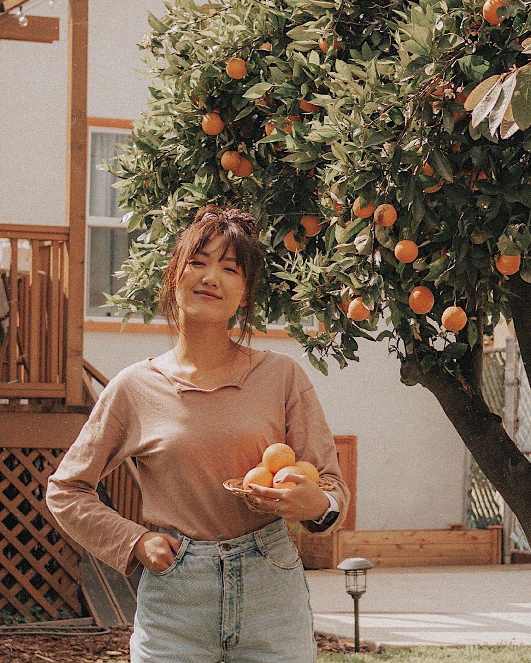 cô gái mặc áo nâu quần jean phong cách thời trang cottagecore trong vườn cam