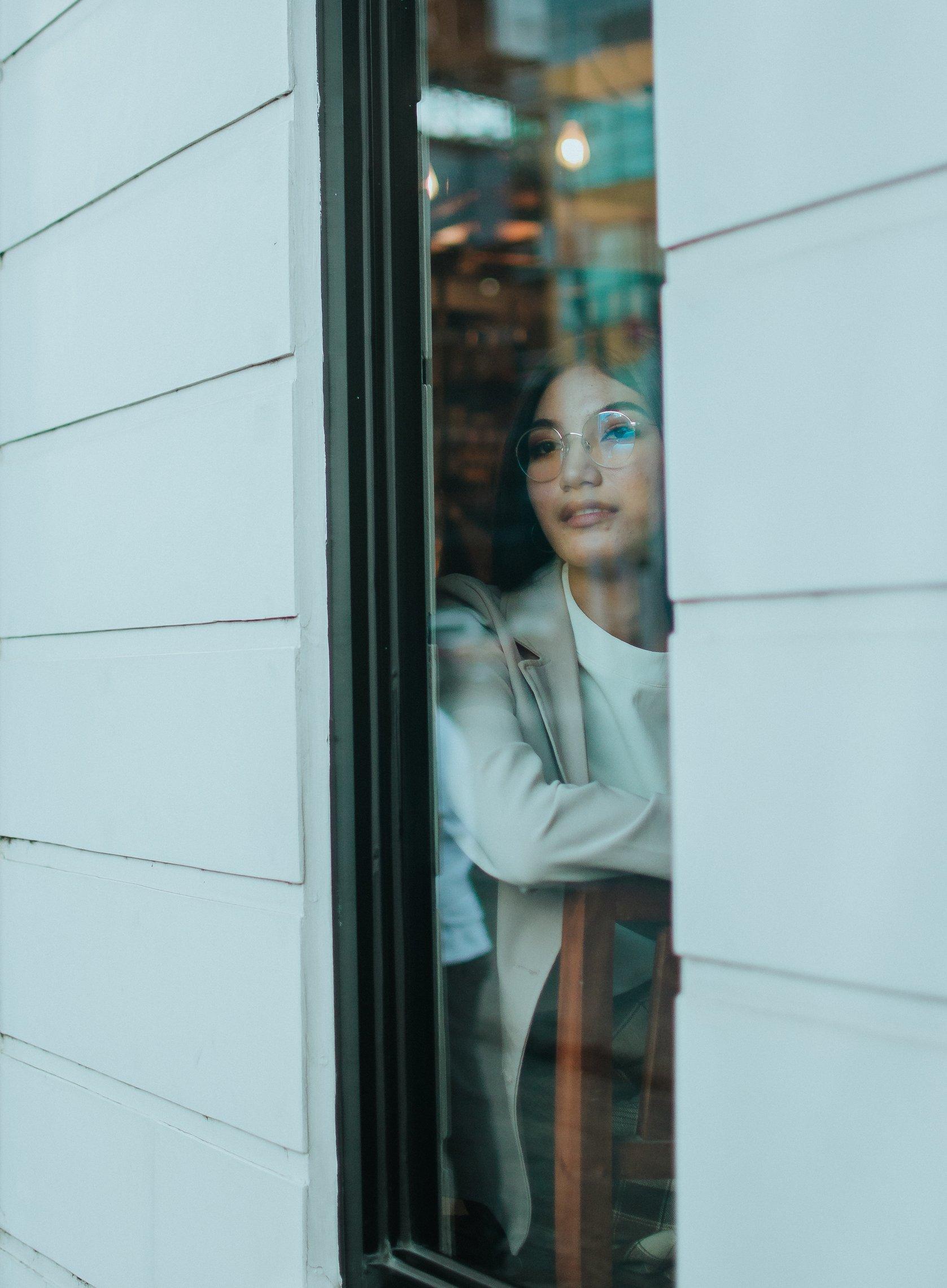cô gái nhìn qua cửa sổ khép kín