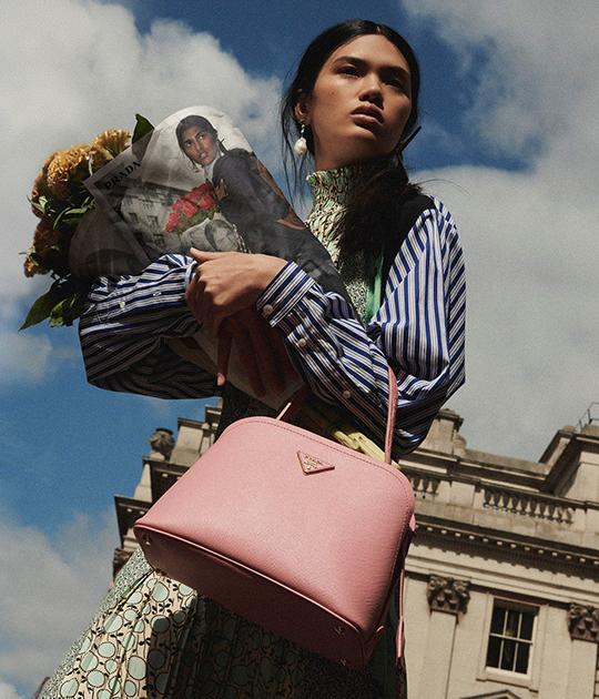 cô gái ôm bó hoa đeo túi xách đồ da hồng mặc áo xanh sọc