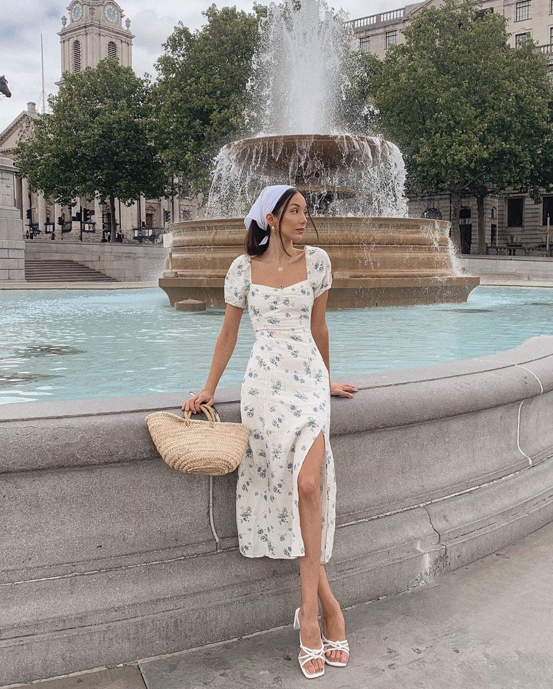 cô gái mặc váy hoa xanh đeo khăn bandana đứng bên đài phun nước