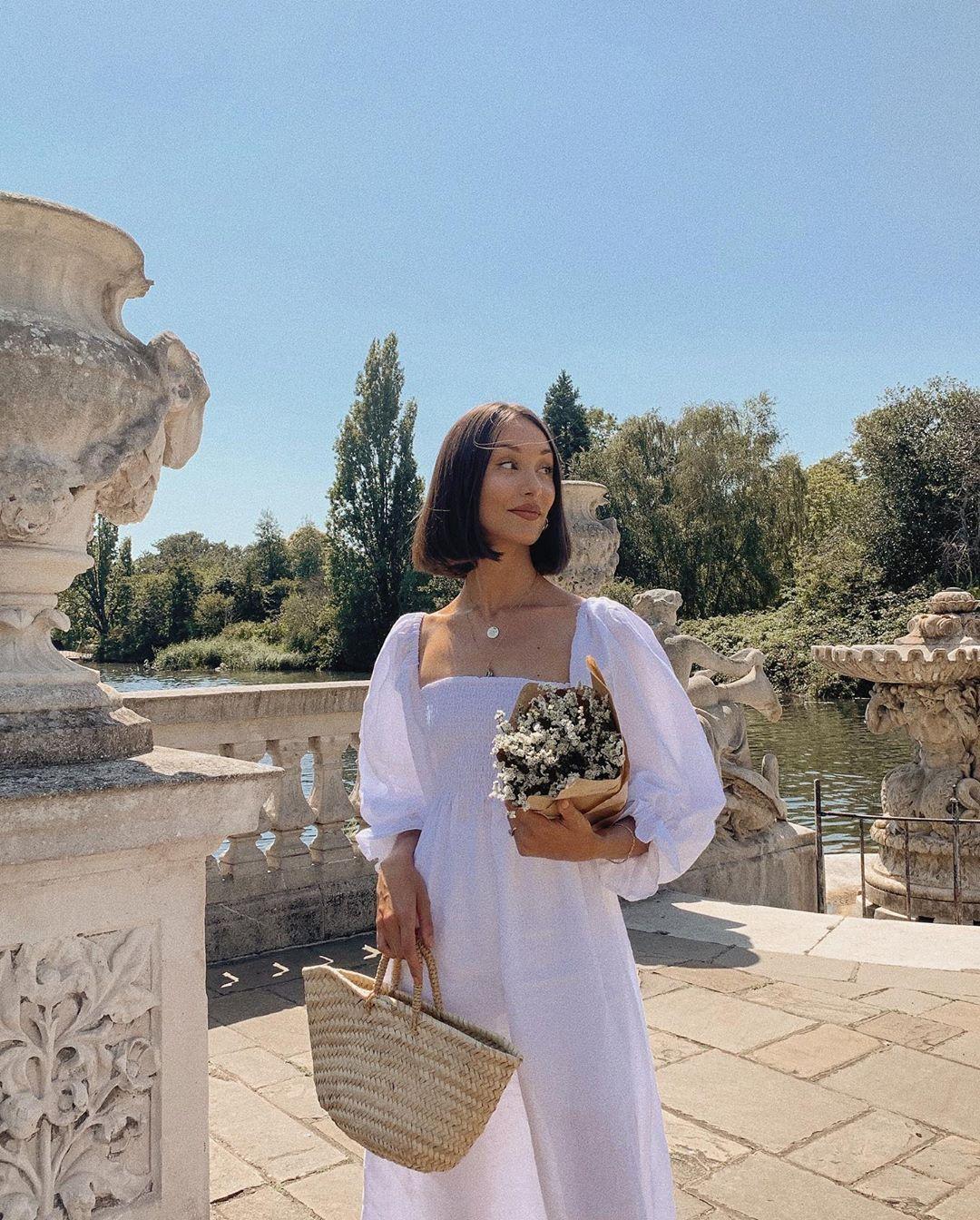 cô gái mặc váy trắng đeo túi cói