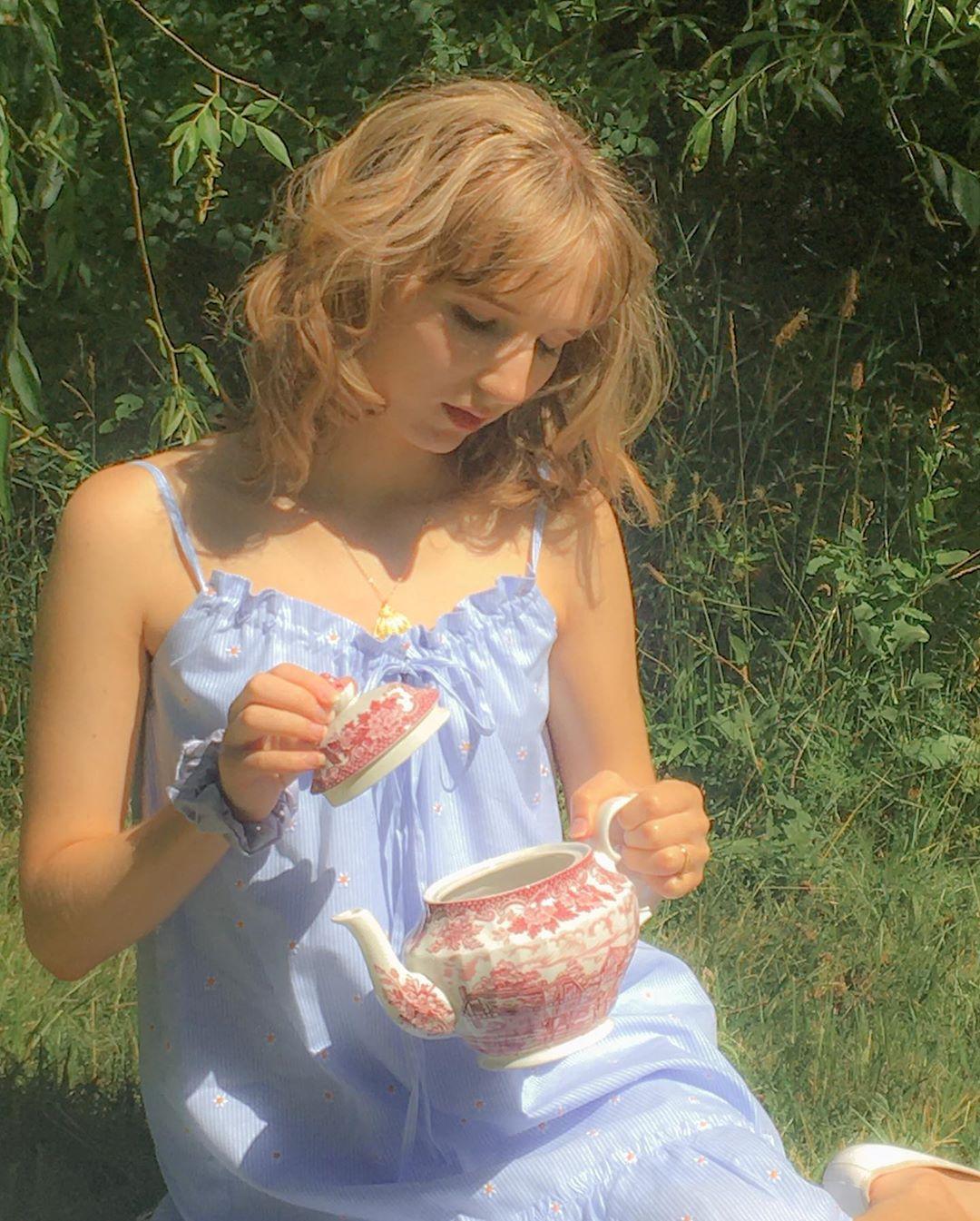 cô gái mặc váy xanh ngồi trên bãi cỏ