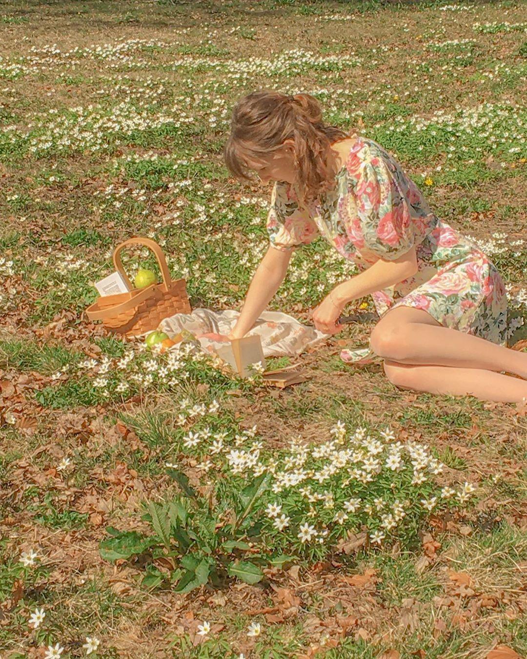 Cô gái mặc váy hoa đọc sách trên bãi cỏ