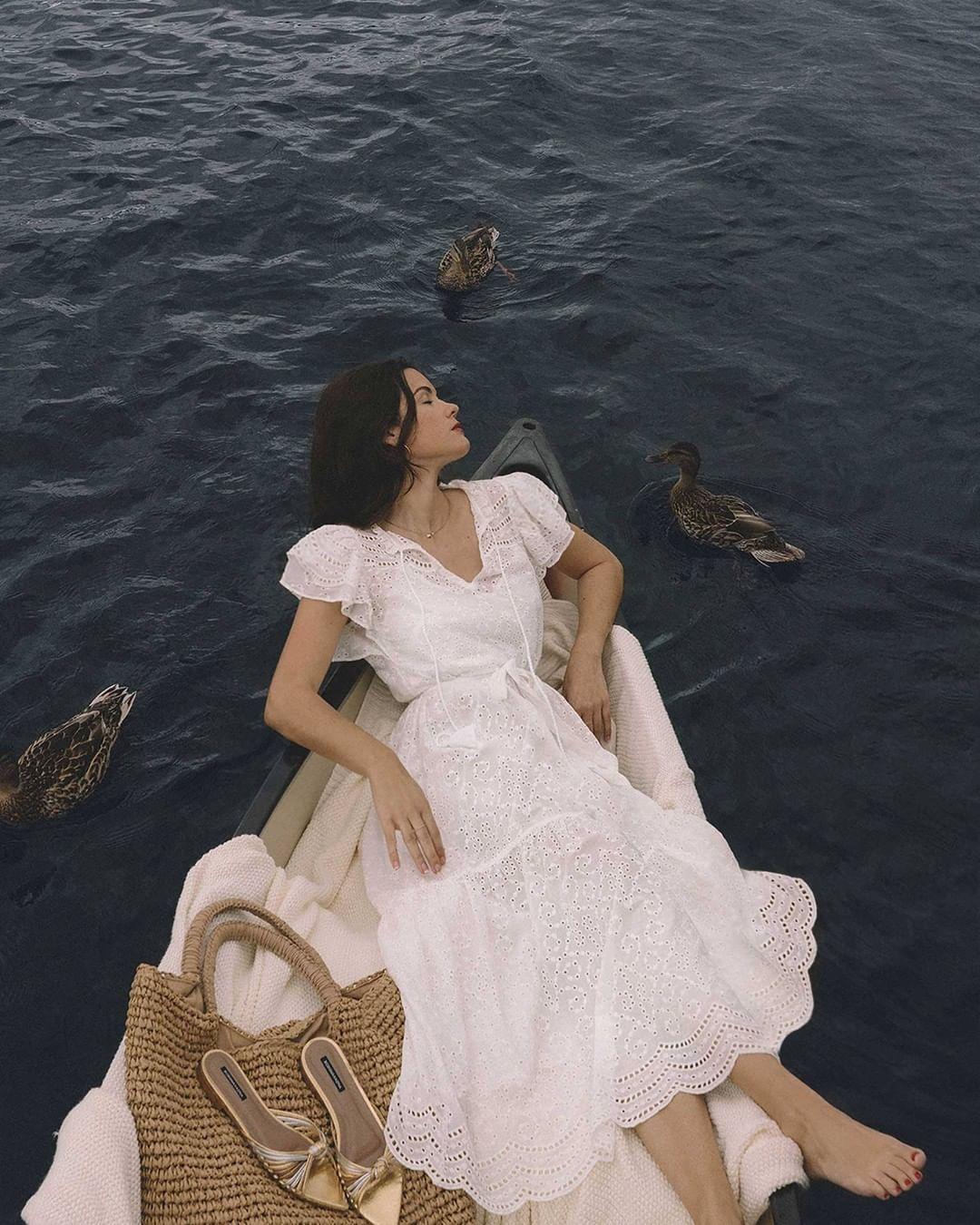 Cô gái mặc váy hai dây trắng cầm bông hoa