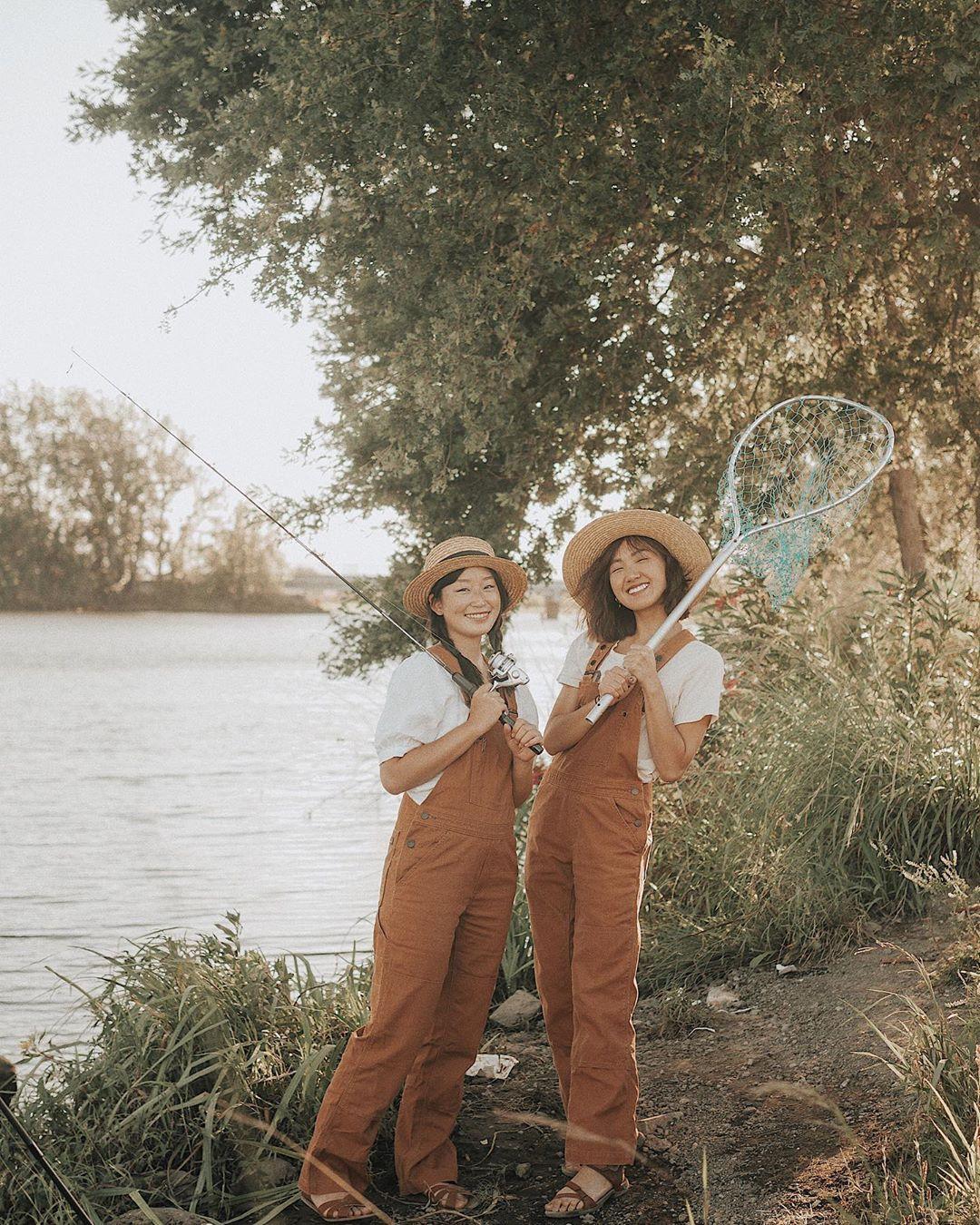 hai cô gái mặc quần yếm nâu áo trắng và vợt câu cá