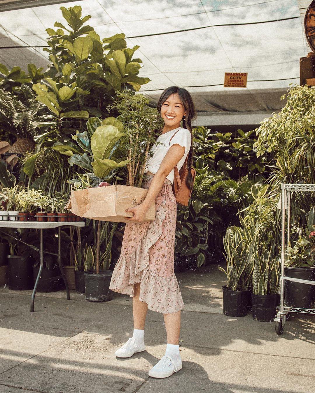 cô gái mặc áo trắng váy bèo hoa ôm chậu cây