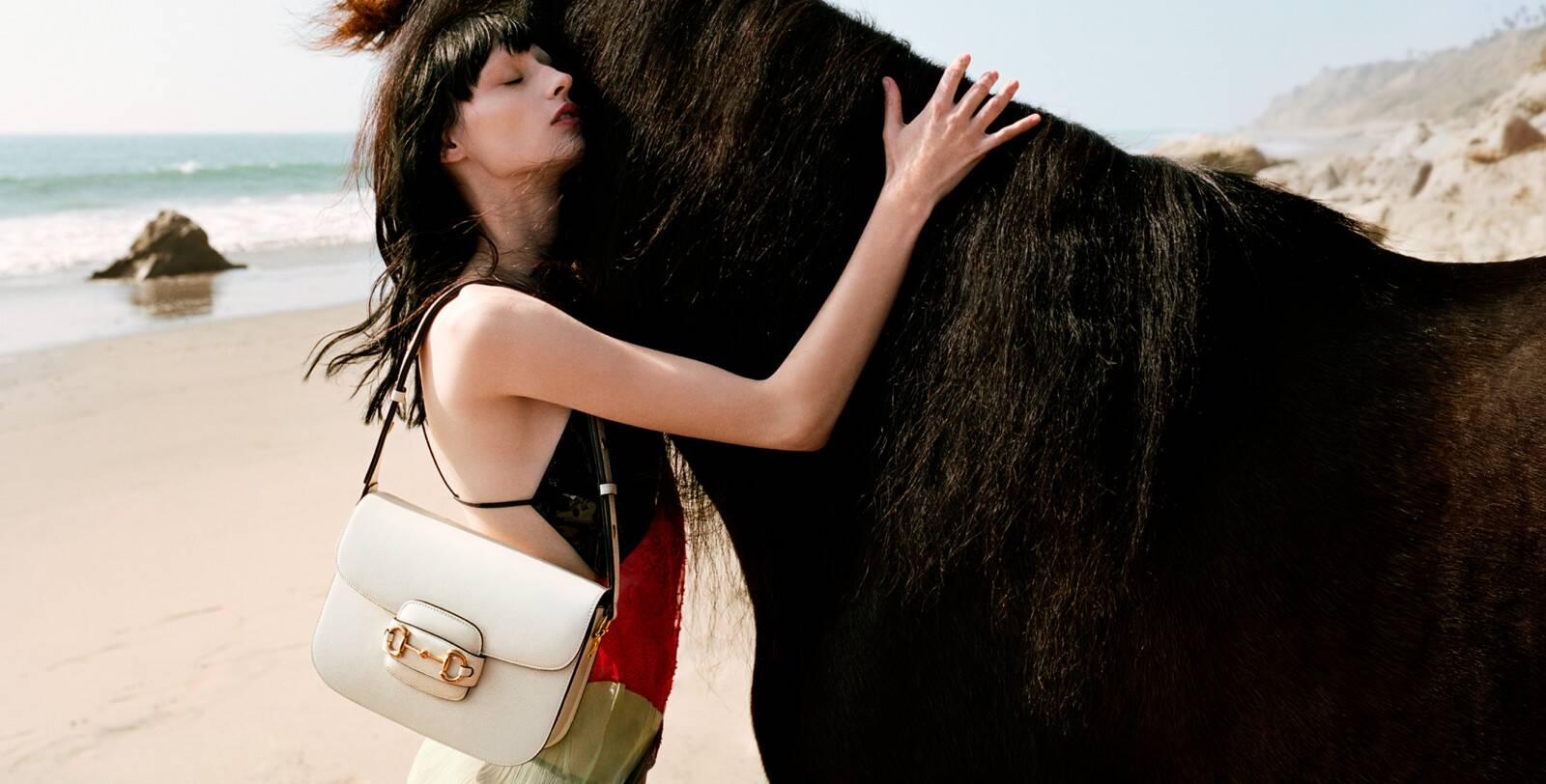 túi xách gucci trắng chụp với ngựa đen